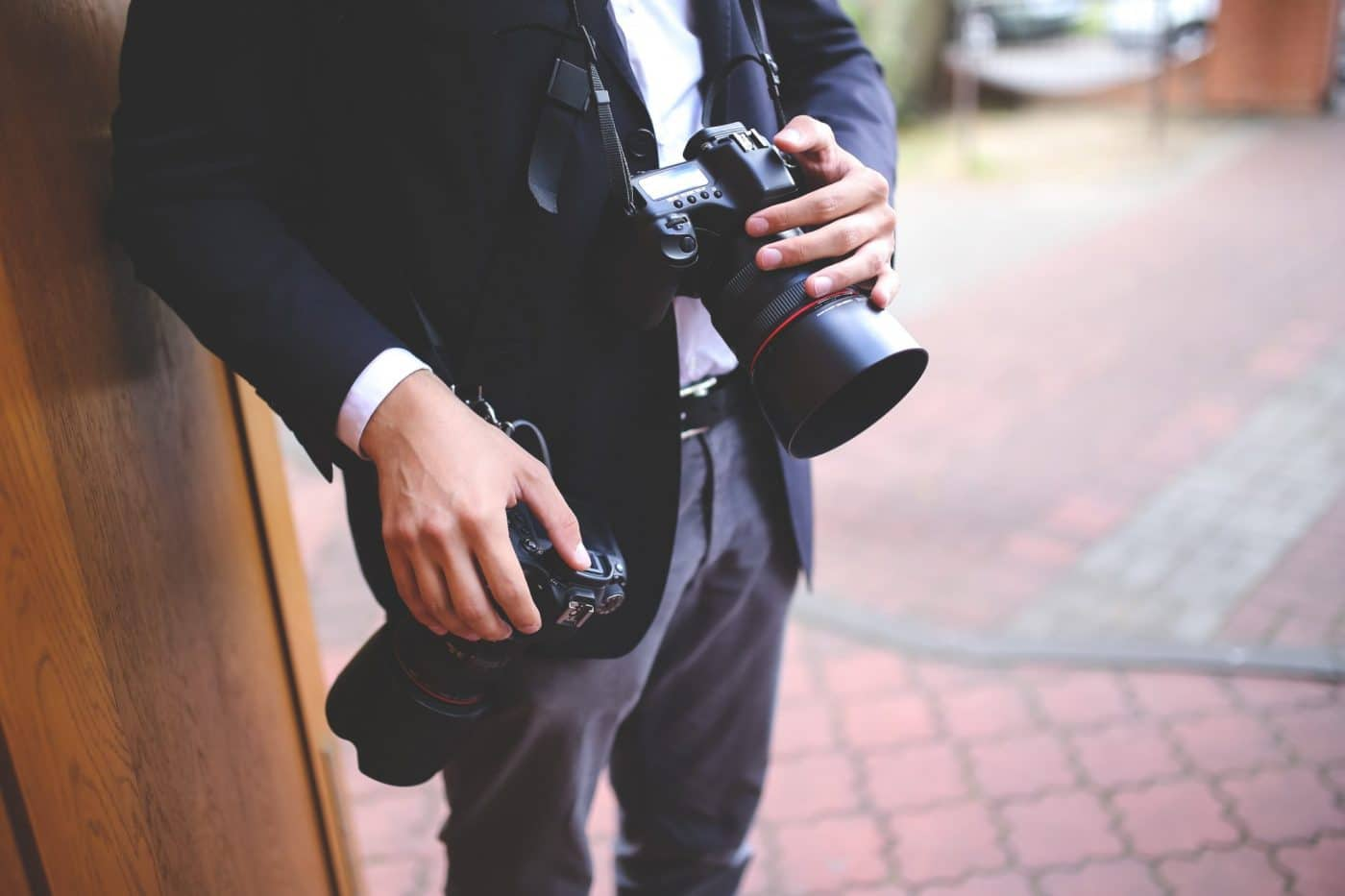 Man holding two cameras for multi-camera shoot